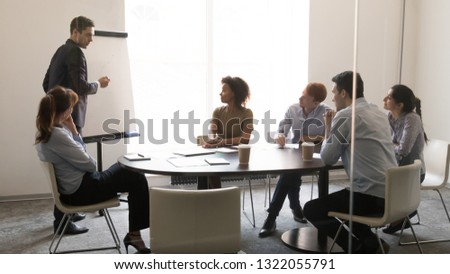 Businessman coach teacher giving presentation on whiteboard at sales team business training, male speaker teaching employees group explaining company strategy at meeting workshop in conference room