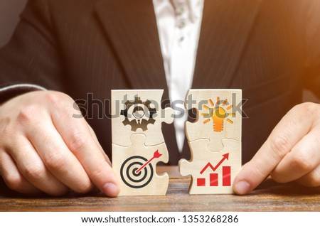 Businessman collects puzzles with the image of the attributes of doing business. Strategy planning concept. Organization of the process. Creating a business model. Management. Research, marketing. Photo stock ©