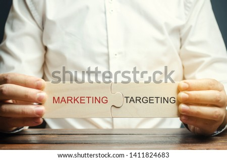Businessman collects puzzles with the word Marketing - Targeting. Business tools. Advertising mechanisms. Improving the efficiency of interaction with the audience. Market management. Target audience #1411824683