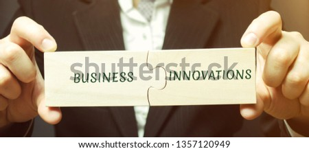 Businessman collects puzzles with the words business and innovations. Innovative ideas for small businesses. Technical, technological and strategic innovation. High tech. Implemented new technologies