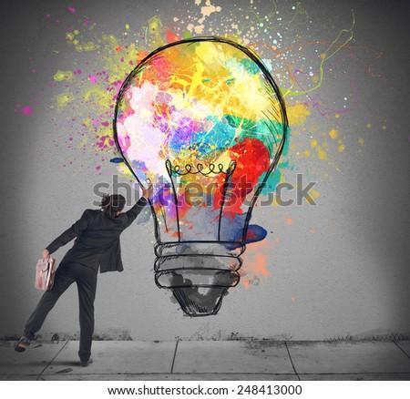 Businessman color with a spray a lightbulb
