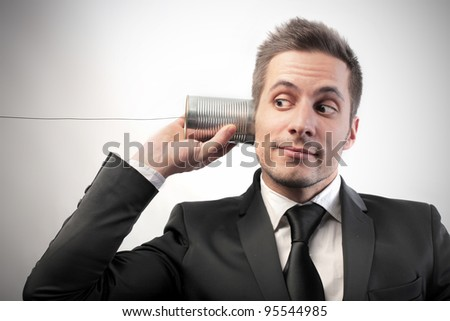 Businessman communicating through a can with a cable as it was a telephone