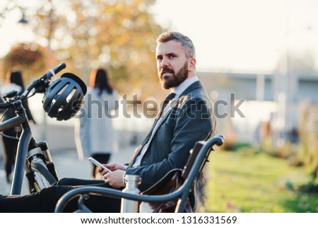 Businessman commuter with bicycle and smartphone sitting on bench in city. #1316331569