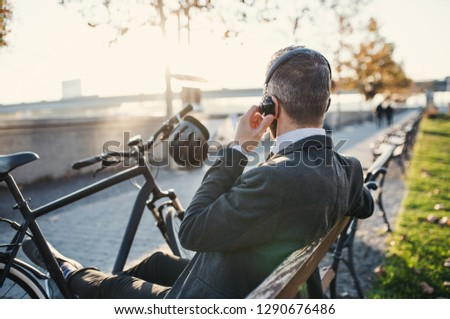 Businessman commuter with bicycle sitting on bench in city, listening to music. #1290676486