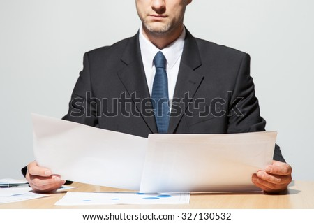 Businessman comparing two documents, neutral background ストックフォト ©