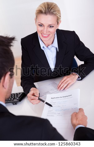 Businessman conducting an employment interview with an over the shoulder view of an application form