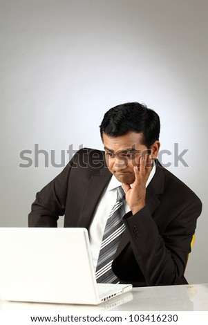 Businessman confused by his laptop - stock photo