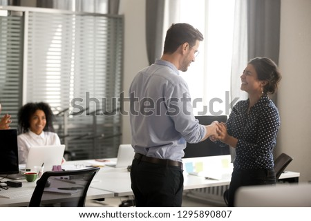 Businessman congratulate indian female successful worker shaking hands in office. Surprised hindu millennial woman feels happy proud getting promotion or reward handshaking with director company boss #1295890807