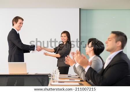 Businessman congratulating Vietnamese manager, her colleagues applauding