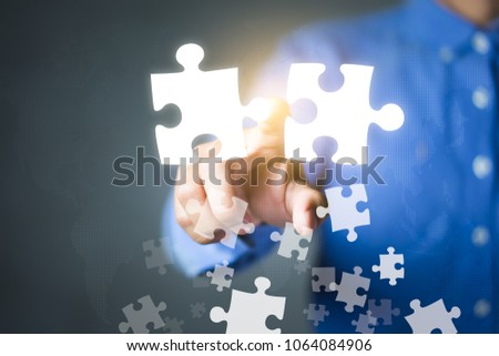 Businessman connecting puzzle pieces. Partnership, Acquisition, Mergers and Joint venture concepts.