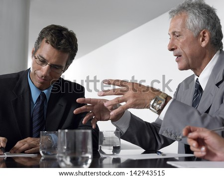 Businessman conversing while male colleague taking notes in conference room