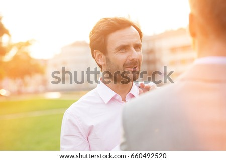 Businessman conversing with colleague at park on sunny day #660492520