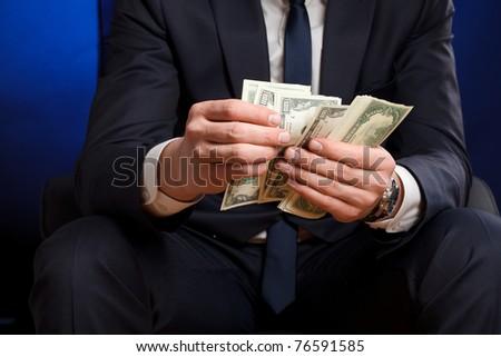 Businessman counts money in hands.