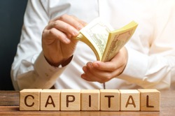 Businessman counts money on the background of the caption Capital. Capitalism, capital increase and influence. Financial liberalization of developing countries, unprincipled withdrawal of capital.