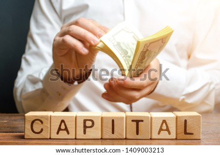 Businessman counts money on the background of the caption Capital. Capitalism, capital increase and influence. Financial liberalization of developing countries, unprincipled withdrawal of capital. Foto stock ©