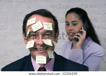 Businessman covered with sticky notes smiling at the camera while a female colleague chats on the phone behind him