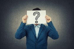 Businessman covering his face using a white paper with drawn question mark, like a mask, for hiding his identity. Isolated gray wall background.