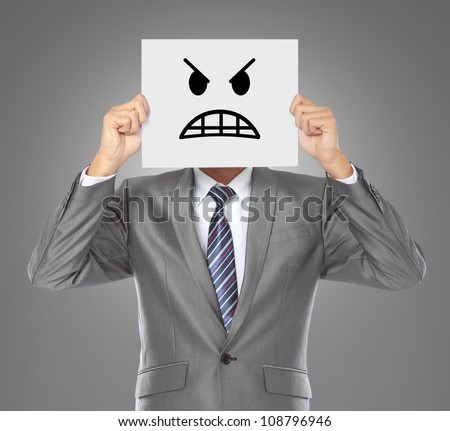 businessman covering his face with angry mask on gray background - stock photo