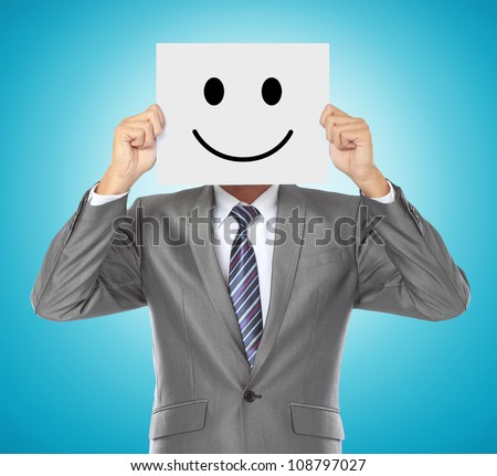 businessman covering his face with smiling mask on blue background