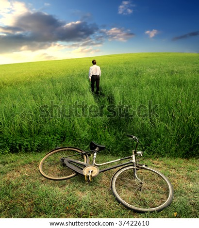 businessman crossing a grass field after a riding bike