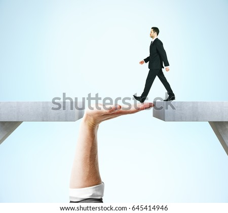 Businessman crossing abstract hand bridge on blue background. Teamwork concept