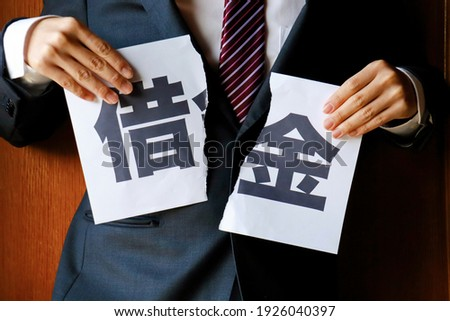 """Businessman cutting a piece of paper marked """"debt"""". Images of debt, loans, and borrowing. Translation: debt."""