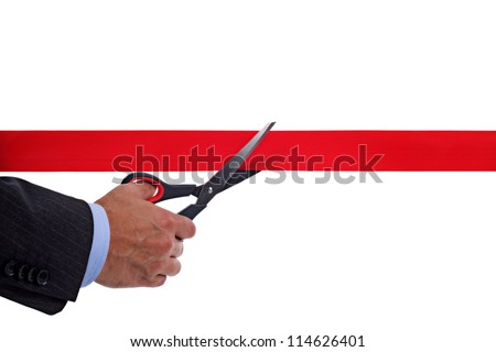 Businessman cutting a red ribbon with a pair of scissors