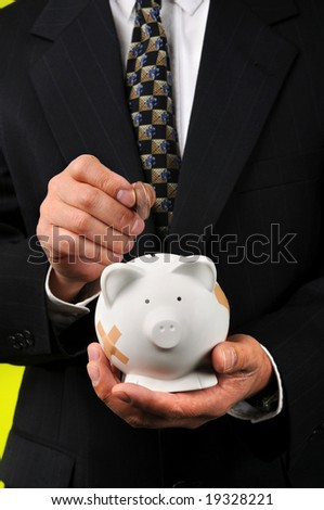 Businessman depositing money into a piggy bank with bandages