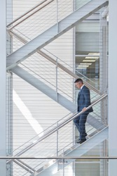 Businessman descending stairs in an office