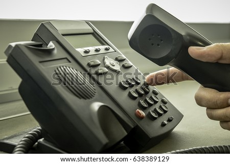 businessman dialing voip phone...