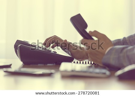 businessman dialing voip phone with pale vintage color effect