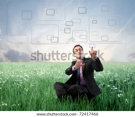 Businessman digitizing on a touchscreen on a green meadow