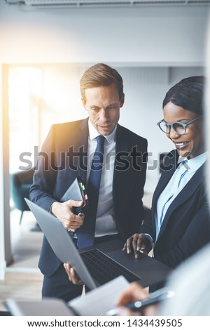 Businessman discussing work on a laptop with a colleague while standing together in a bright modern office