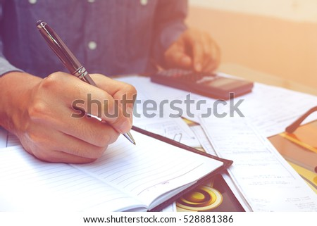 Businessman doing finances with using calculator and writing note in office.