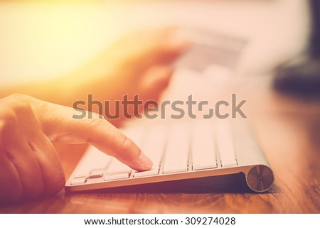 Businessman doing online banking, shopping, making a payment or purchasing goods on the internet entering his credit card details on a pc, close up view of his hands. Vintage filter