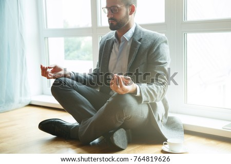 businessman doing yoga in lotus pose #764819626