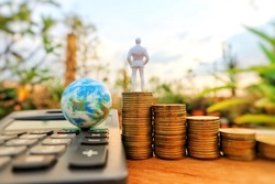 Businessman doll miniature stands on top roll ladder step of coin money and world globe on calculator in blur natural tree bright light