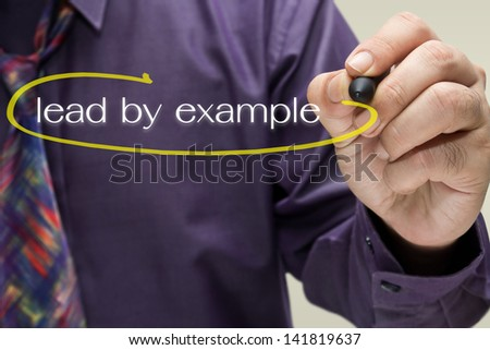 Businessman draw a circle mark on Lead By Example text