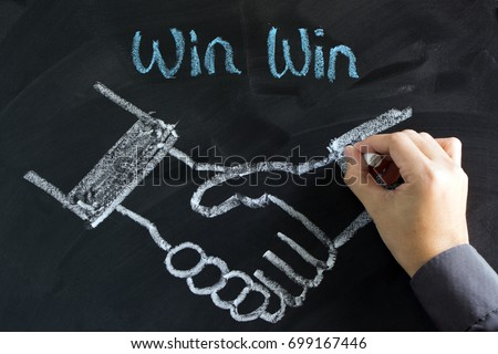 Businessman draw a handshake on chalkboard for win win strategy concept