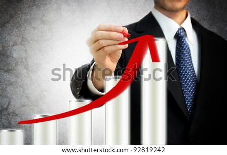 Businessman drawing a rising arrow on the top of bar graph representing growth - stock photo