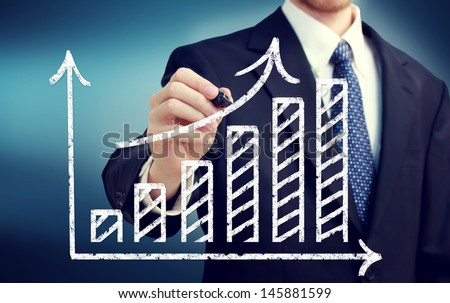 Businessman drawing a rising arrow over a bar graph