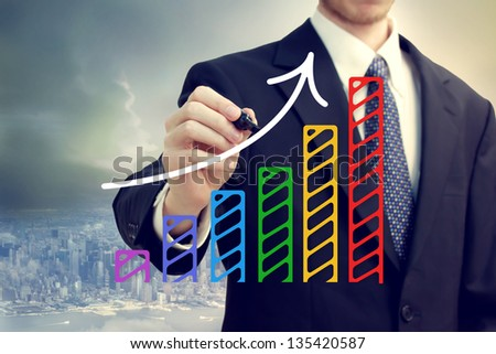 Businessman drawing a rising arrow over a bar graph above the city