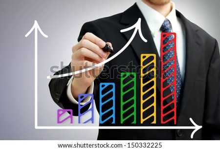 Businessman drawing a rising arrow over a colorful bar graph