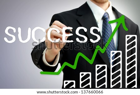 Businessman drawing a rising arrow over a growing bar graph showing success