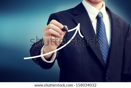 Businessman drawing a rising arrow over blue background