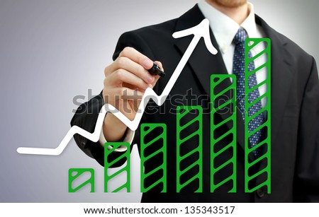Businessman drawing a rising arrow over growing green bar graph