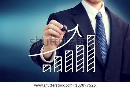 Businessman drawing a rising arrow over the bar graph