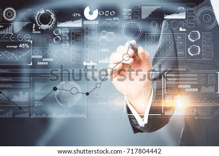 Businessman drawing abstract business chart hologram on blurry office interior background. Network concept. Double exposure