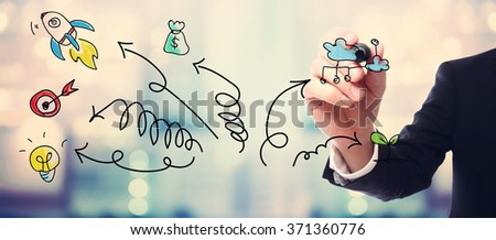 businessman drawing arrows and...
