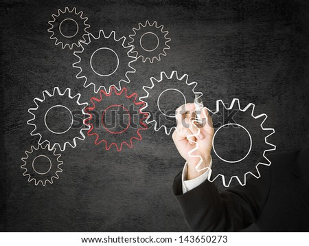 Businessman drawing cogwheels - networking or cooperation concept
